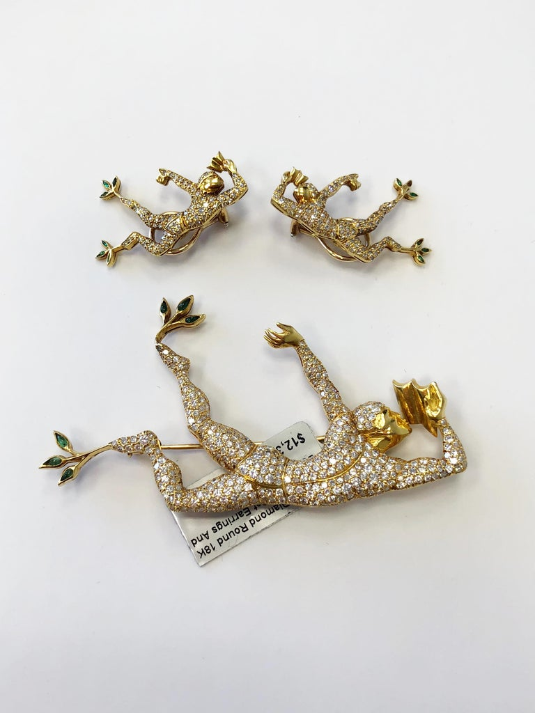Stunning set of a man dancing made with 6.50 carats of white good quality diamonds and emerald accents.  These pieces are very artistic and dainty.  They are made with 18k yellow gold and are made well.  The earrings are french clip and are