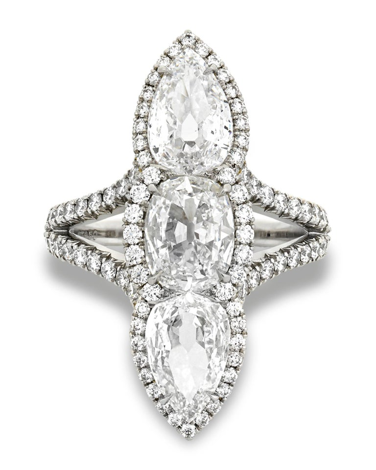 Three incredible, certified white diamonds totaling 3.04 carats are simply radiant in this three-stone North-South ring. The cushion-shaped center stone weighs 1.06 carats and displays a D color with VS2 clarity. The pear-shaped diamonds weigh a