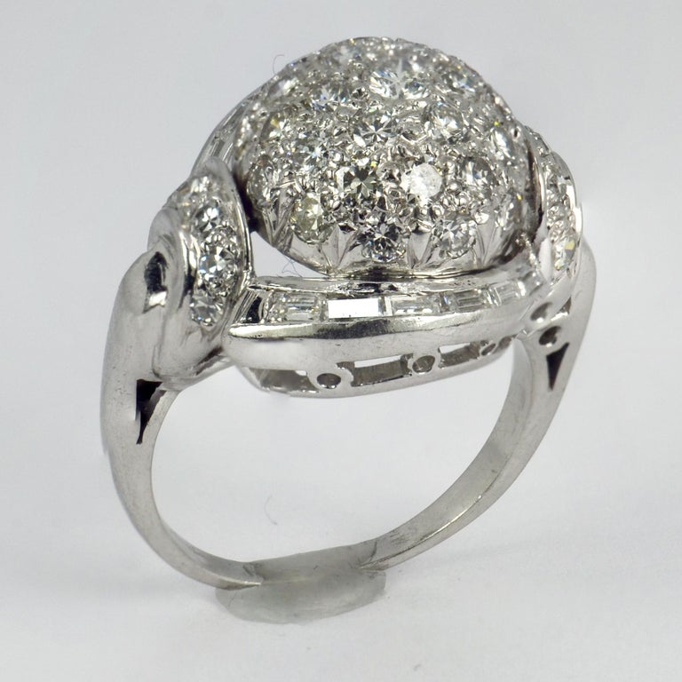 A platinum and white diamond cocktail ring designed as a dome with a curve of tapered baguette diamonds to each side and diamond set shoulders. The ring is set with 41 round brilliant cut white diamonds and 12 baguette cut diamonds. Unmarked but