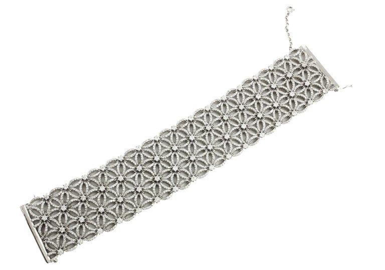 Shining and elegant carpet bracelet in 14 K white gold realized with flower theme all studded by top quality little white diamonds  Diamonds 16.87 ct  Total Weight 73.70 g  R.F + oohui Length 18 cm  Width 3.2 cm   For any enquires, please contact