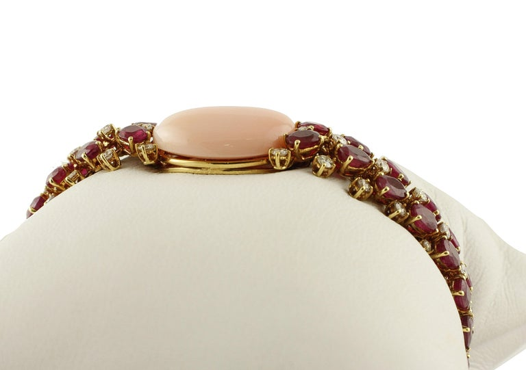 Amazing bracelet in 14K rose gold mounted with 3.18 ct of white diamonds rows and 31.20 ct of two rubies rows. In the center there is a gorgeous piece of angel skin pink coral (3.40 g). Diamonds 3.18 ct  Rubies 31.20 ct  Angel Skin Pink Coral 3.40 g
