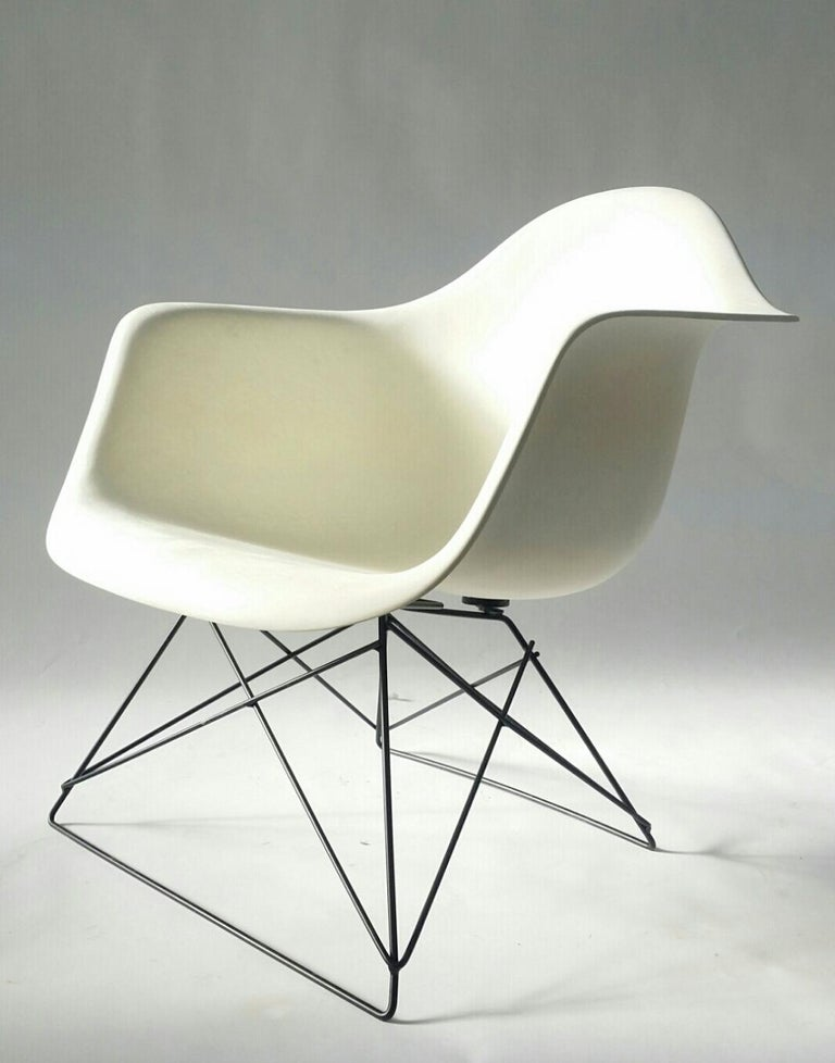 White Eames arm shell chair, produced by Herman Miller, circa 1972, on black 'cats cradle' base. We would describe this Eames fiberglass arm shell as