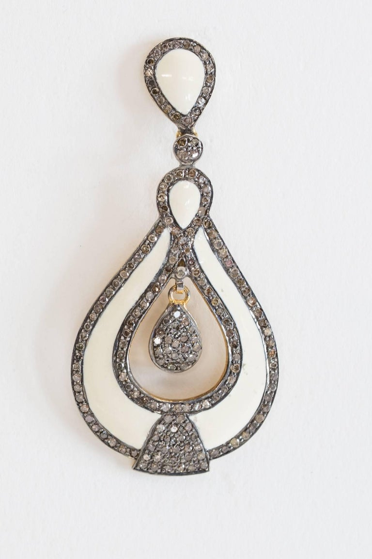 White enamel earrings with pave`-set diamonds set in oxidized sterling silver with 18K gold post for pierced ears.  Carat weight of diamonds is 2.54.