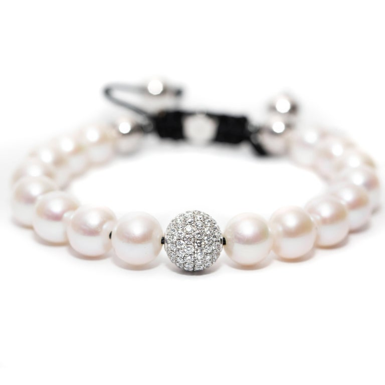 This Contemporary fresh water Pearl Bracelet features an adjustable Cord further highlighted with a Pave set 1.80 Carat Round Brilliant Color G Clarity VS Diamond sphere set in 18 Karat White Gold for a luxurious feel. Available in a choice of