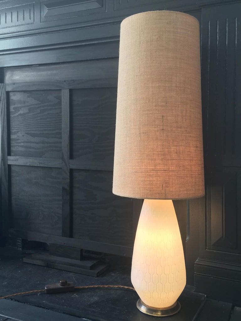 White glass Mid-Century Modern table or floor lamp with brass base and three-way switch, European.   The lamp base is made of white satin glass with a raised geometric pattern, and is fitted with a three-way switch allowing light to come through the