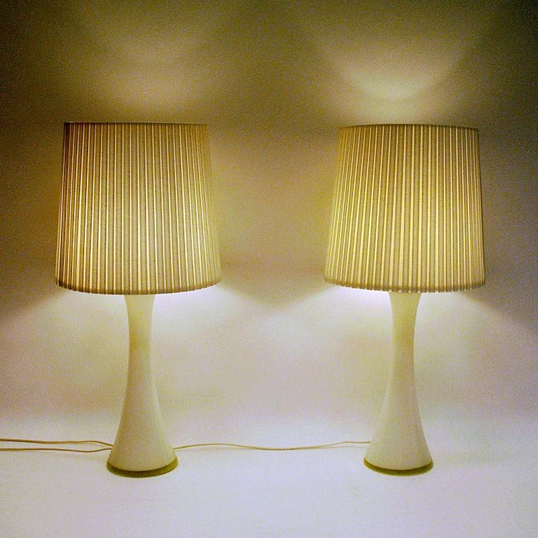 Elegant pair of white glass tablelamps by Bernt Nordstedt for Bergboms AB Sweden in the 1960s. Diabolo shaped and with teak lids on top. Marked with makers mark underneath: Bergboms.  Measures: Height about: 45 cm H. (incl bulb socket) Lampfoot 15