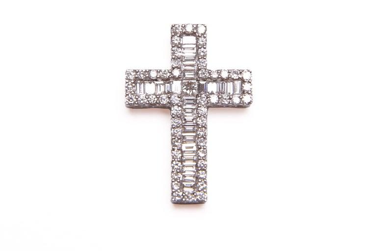 A truly dazzling diamond full set 18 carat white gold cross / crucifix pendant; this brilliant piece comprises central princess cut diamond, a surround of twenty-five baguette diamonds and fifty-two round brilliant cut diamonds. The total diamond