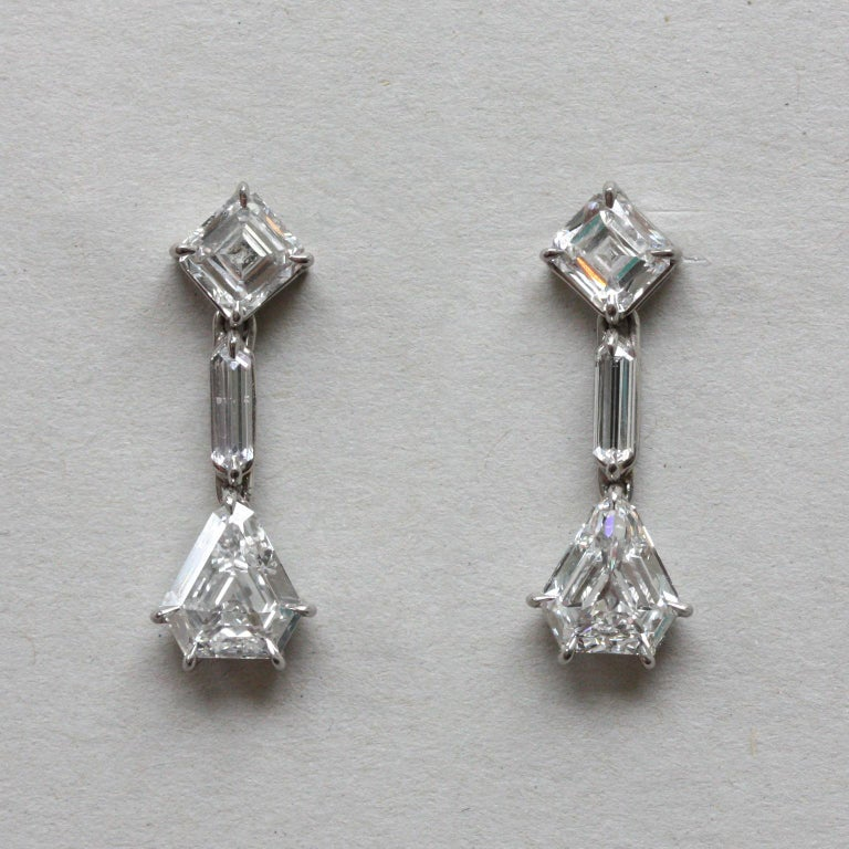 A pair of white gold earrings with diamonds, in the top asscher cut diamonds that are turned a quarter (each app. 0.70 carat), under which a long pointy baguette cut diamonds (app. 0.2 carats) and at the bottom a kite or shield cut diamonds ( each