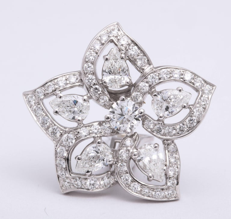 Romantic 18 Karat white gold 5-petal floral earrings mounted with floating pear-shaped diamonds within a trim of pave'-set round brilliant-cut diamonds, total weight: 3.82 carats.  Fitted with French clip and post for pierced ears.  Can be worn with