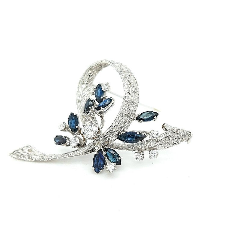 Attractive white gold brooch set with diamonds and sapphires.  Fine and glamorous brooch to make you sparkle on every occasion.  Diamonds: Brilliant cut diamond, together 0.90 carat  Sapphires: 9 Marquise cut sapphire precious stones, together 3.1