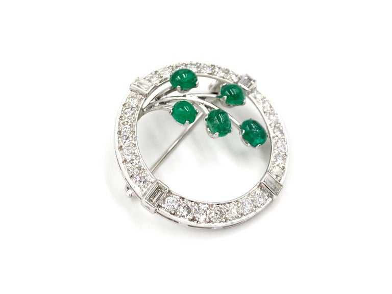 An elegant and wearable 14k white gold diamond and emerald vintage brooch with a beautiful garland branch motif. Circle brooch is composed of approximately 1.25 carats of white round brilliant and baguette cut diamonds at approximately G color, VS2
