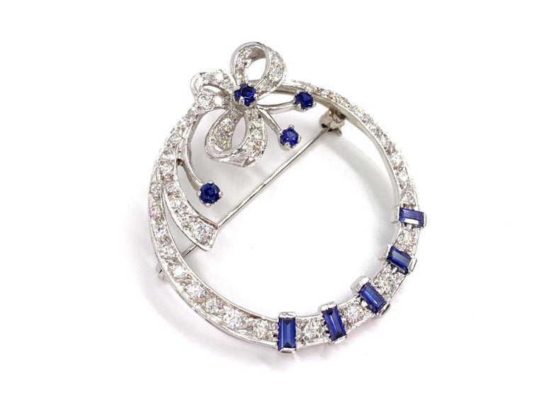 An exquisite 14 karat white gold bow garland style circle brooch featuring high quality blue sapphires and diamonds. Brooch has an approximate diamond total weight of 2 carats at approximately G color, SI1 clarity. Nine vivid, very well saturated