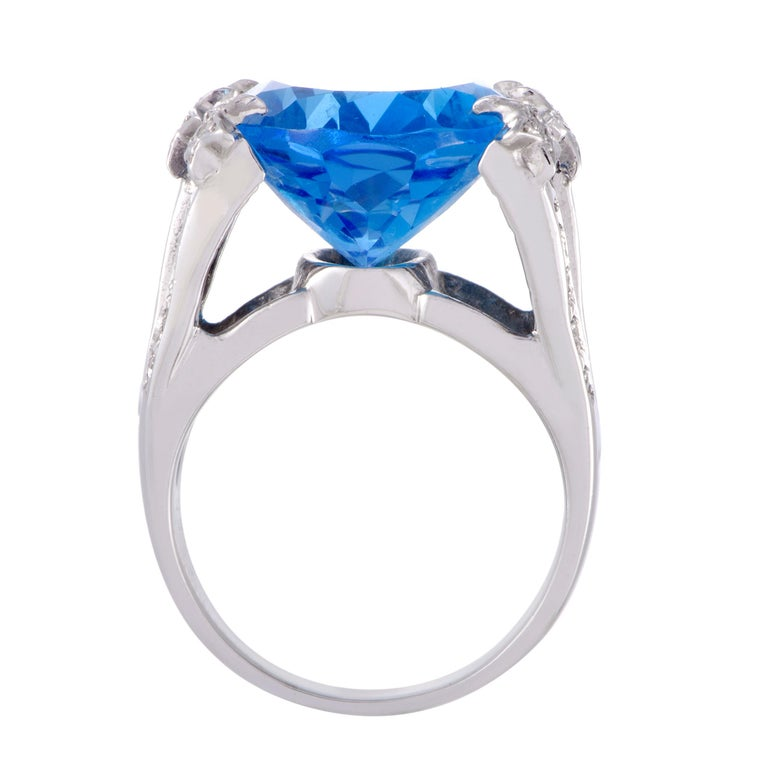 Provided a brilliant pedestal in the form of shimmering 14K white gold and resplendent diamonds weighing in total 0.26ct, the astonishing topaz weighing 25.77 carats compels with its attractive color, neat cut and sheer size.  Ring Top Dimensions: