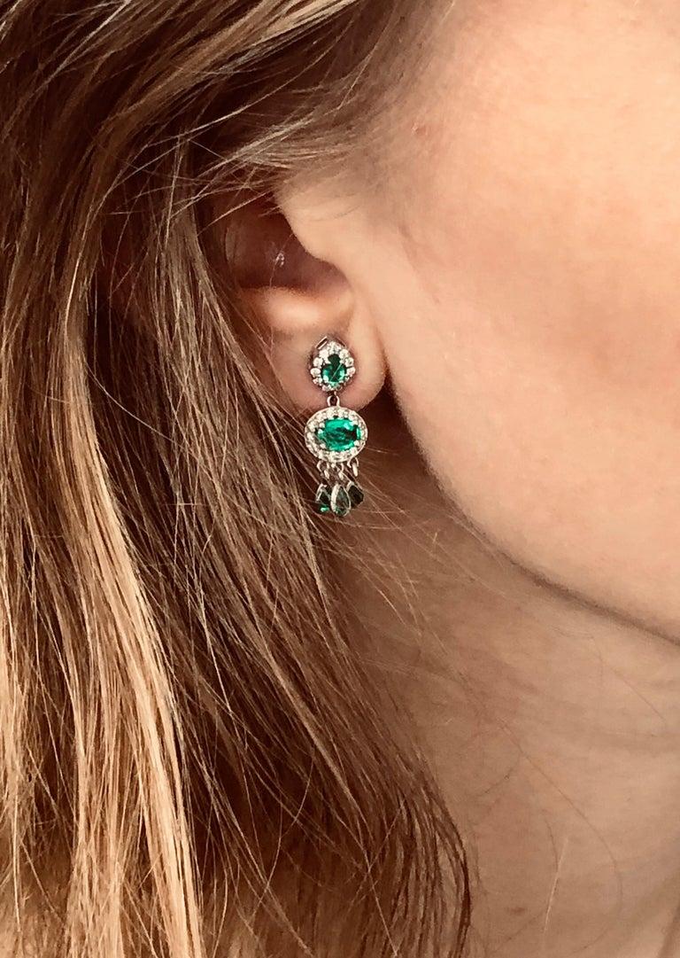 Eighteen karat white halo diamond and emerald gold drop measuring 1 inch dangle earrings Pear shape emerald alternating with oval shape emerald diamond halo design with six dangle pear shape emerald  Emeralds weight 2.70 carats  Diamond weight 0.75