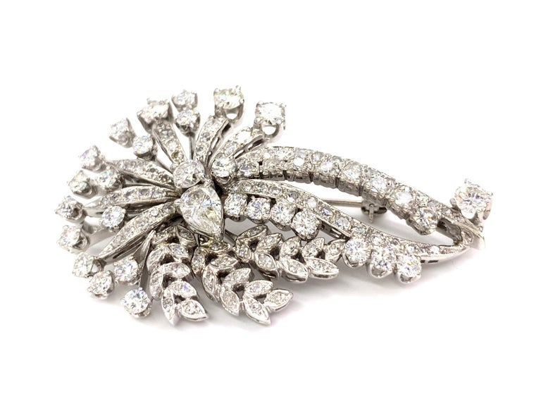 Circa 1950's, an elegant and flowing diamond spray brooch that doubles as a slide pendant, made with approximately 4.50 carats total weight. Designed in 14 karat white gold, this exquisite piece is reminiscent of a floral bouquet with leaf and