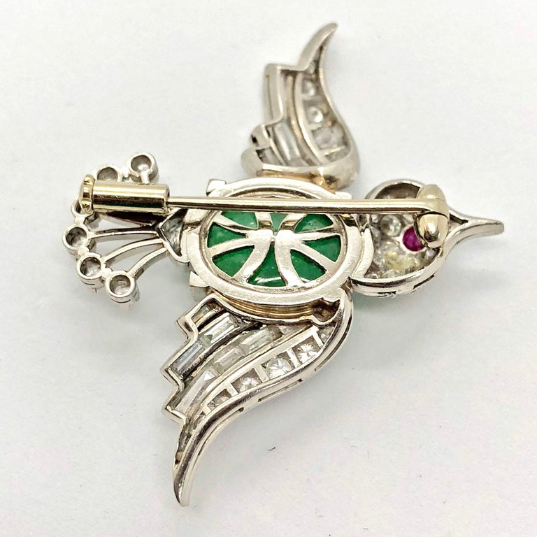 A cute late Art Deco bird brooch, circa 1940s. The bird body centres an emerald cabochon, weighing ca. 6 carats. The eye is made out of a ruby cabochon and the feathers and head of the bird are artistically studded with diamond round brilliants,
