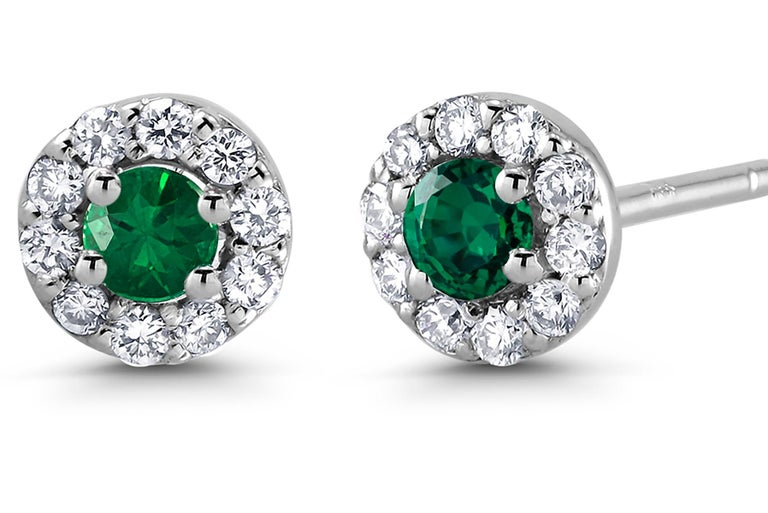 14 karat white gold halo emerald and diamond earrings  Emerald weight 0.20  Diamond weighing 0.27 carat New Earrings Width 0.25 inch Emerald hue tone color deep forest green  The halo setting is a setting that encircles any shaped gemstone with tiny