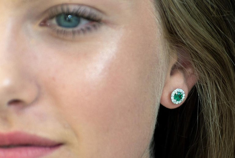 Featuring 18k white gold halo emerald and diamond earrings  Measuring 0.35