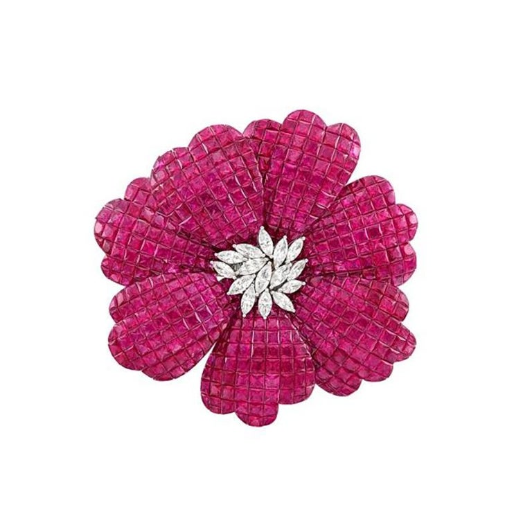 A White Gold, Invisibly-Set Ruby and Diamond Flower Brooch 18 kt., the petals of square, ruby and fancy-shaped rubies approximately 73.48 cts., centering a cluster of 15 marquise-shaped diamonds approximately 1.46 cts., approximately 22.3 dwts.