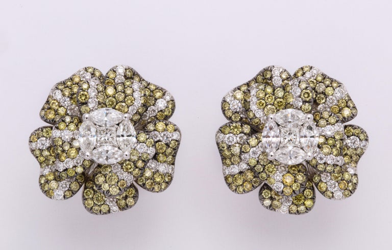 Bright and happy 18K white gold floral earclips composed of individual petals adding animated breath to the complete flower.  Completely pave'-set with natural color round brilliant cut greenish yellow diamonds, and wisps of colorless diamonds,