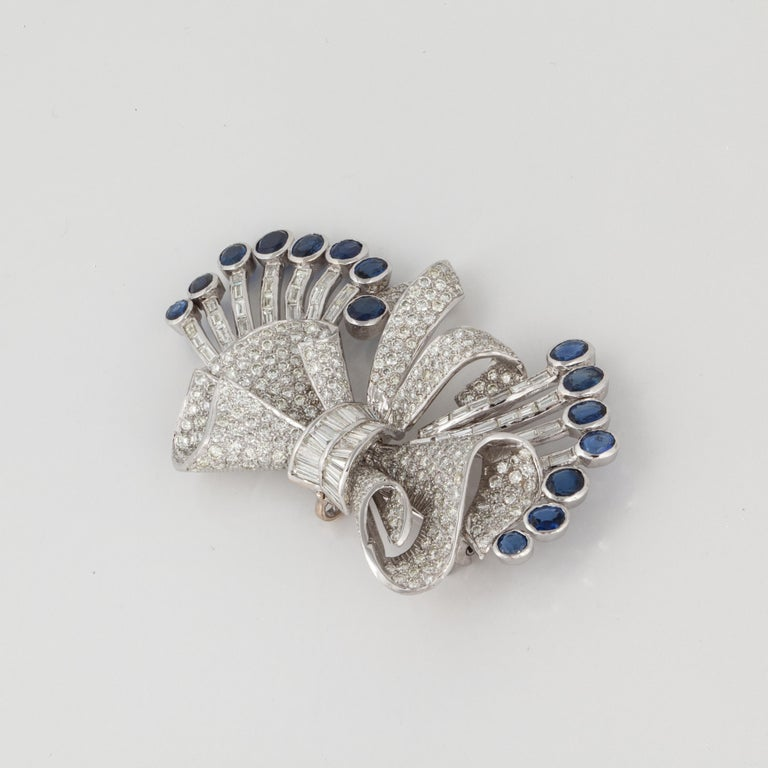 18K white gold bow pin.  Set with fifteen (15) oval sapphires totaling 8.50 carats.  In addition, there are 292 round diamonds and 49 baguette diamonds.  Total diamond weight is 15.4 carats; they are G-I in color and VS in clarity.  There is also a