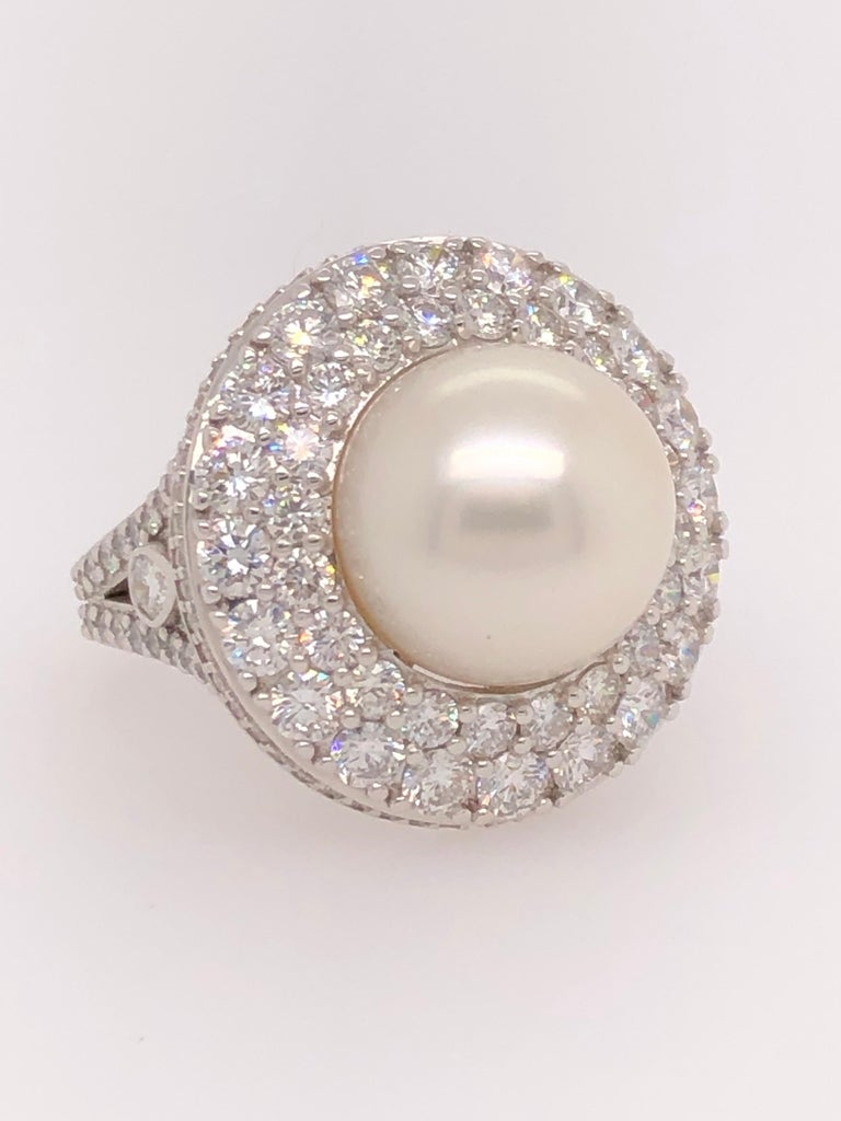 Pearls and diamonds, a classic combination for all time. This stunning ring exudes refinement and dignity. It is strong but elegant like you.   One 14.5 millimeter Tahitian pearl sits center of the circular 18K white gold setting with a total weight