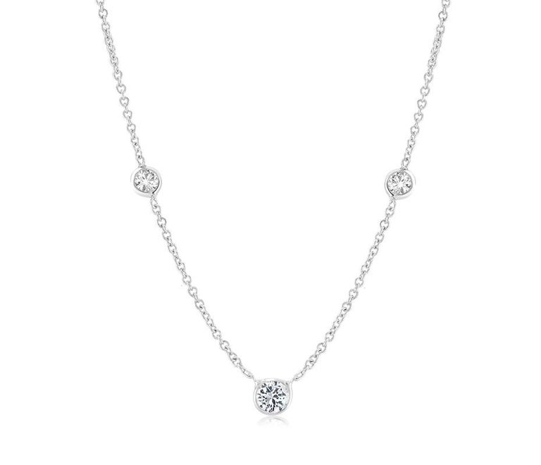 Fourteen karat white gold necklace pendant with three graduating bezel-set diamond  Measuring 16 inch long Center Diamond weight 0.15 carat Two side Diamonds weight 0.05 carat each  Thin cable chain necklace with spring lock: a lock that fastens