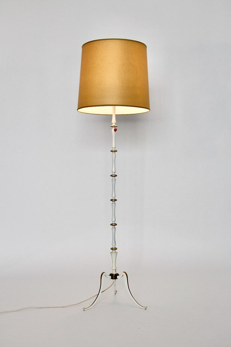 Mid-Century Modern white and golden vintage floor lamp from metal designed and executed 1950s Italy. The floor lamp, which was designed in the mid century modern era in Italy features golden lacquered details and a white stem. Its Hollywood
