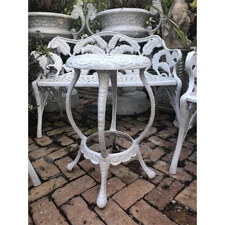 White Hollywood Regency wrought iron Patio Furniture set in Fern or Palm design. Set includes two tables with arms, one bench with arms, and one small round table.   The back of each chair and bench features a lovely fern or palm design up the back