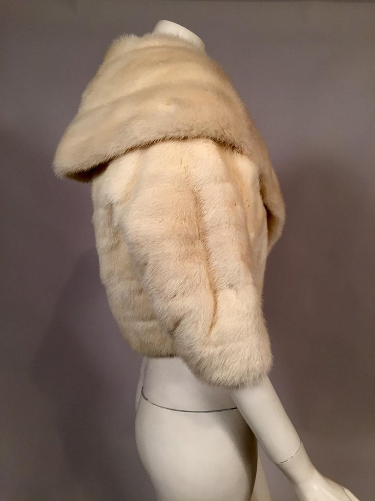 This gorgeous white mink jacket has a generous shawl collar and the pelts are worked horizontally throughout. The jacket closes with a single fur hook at the center front and it is lined with and ivory and gold metallic brocade. There is an interior