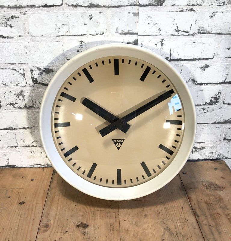 This wall clock was produced by Pragotron in former Czechoslovakia during the 1960s.It features a white bakelite frame, aluminium dial and clear glass cover. The piece has been converted into a battery-powered clockwork and requires only one