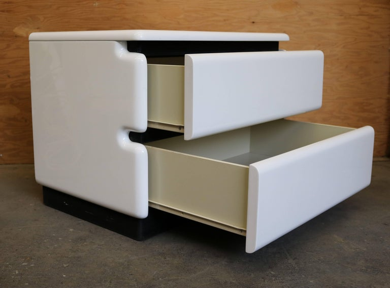 Gloss white lacquered Minimalist nightstands each feature two pull-out drawers and have a black corrugated detail between each drawer. Made in the 1970s by Maison Rougier.