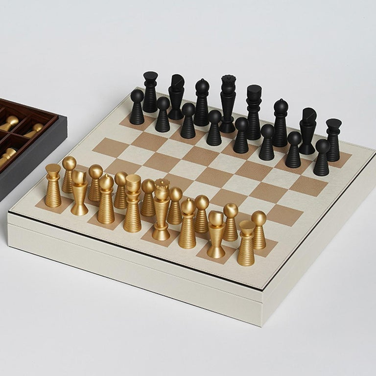 Dynamic and elegant, this chess board set will make a sublime accent in a modern or traditional home. Crafted of walnut, the box is upholstered in white leather and accented with gold board squares for the chessboard surface, while the interior