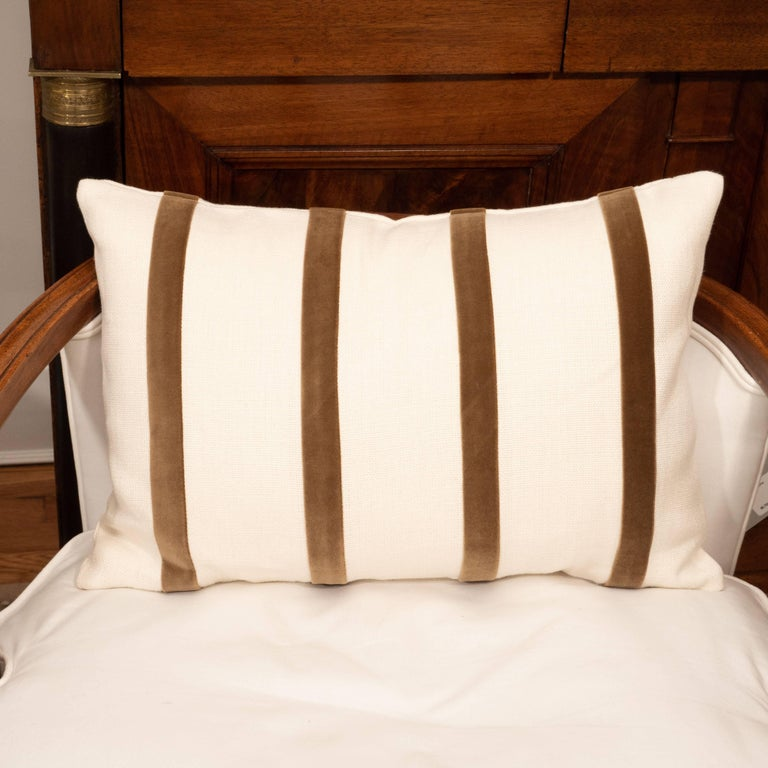 A white linen pillow with brown velvet stripe.