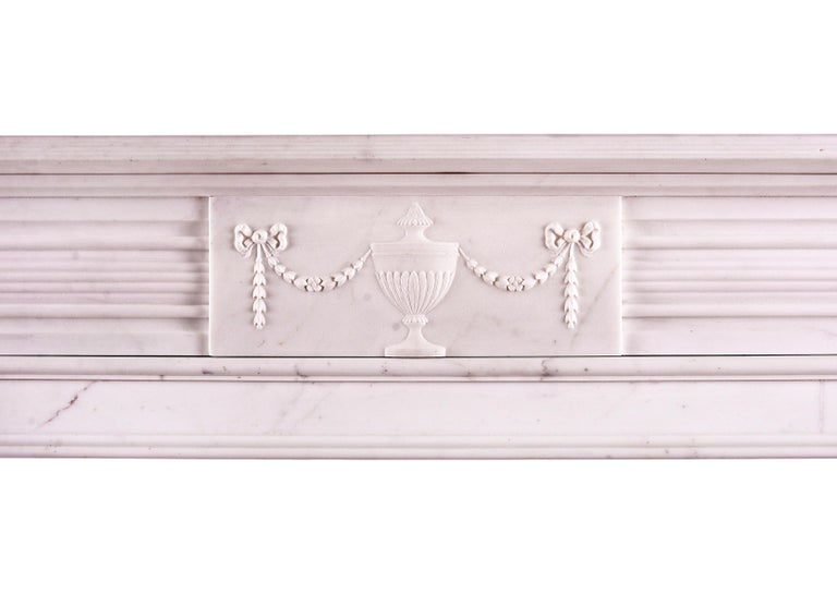 A white marble fireplace in the Regency style. The fluted jambs surmounted by finely carved paterae, the frieze with centre block featuring swags, flowers and classical urn. Reeded shelf above. English, circa 1900.  Shelf Width        1464 mm    57