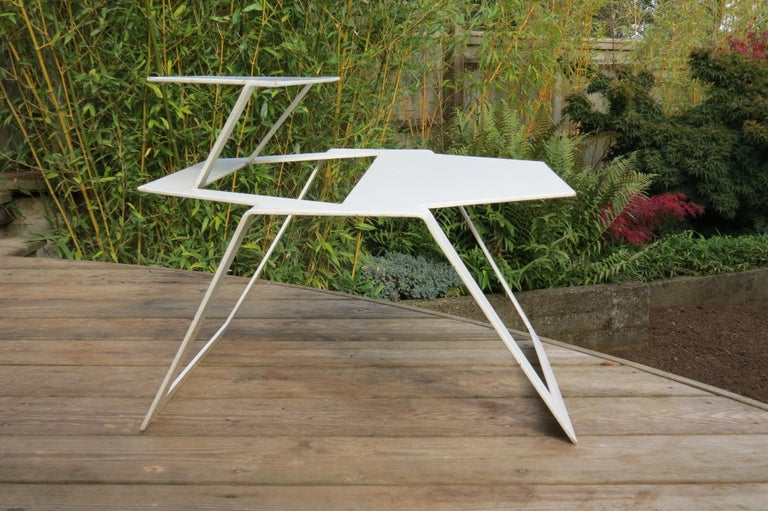 A very good quality metal table from the 1990s, good quality thick steel. Very cleverly cut and formed from one sheet of metal. Possibly a prototype. Good over all condition, some wear and minor loss to the paint and distressing over all.  Price is