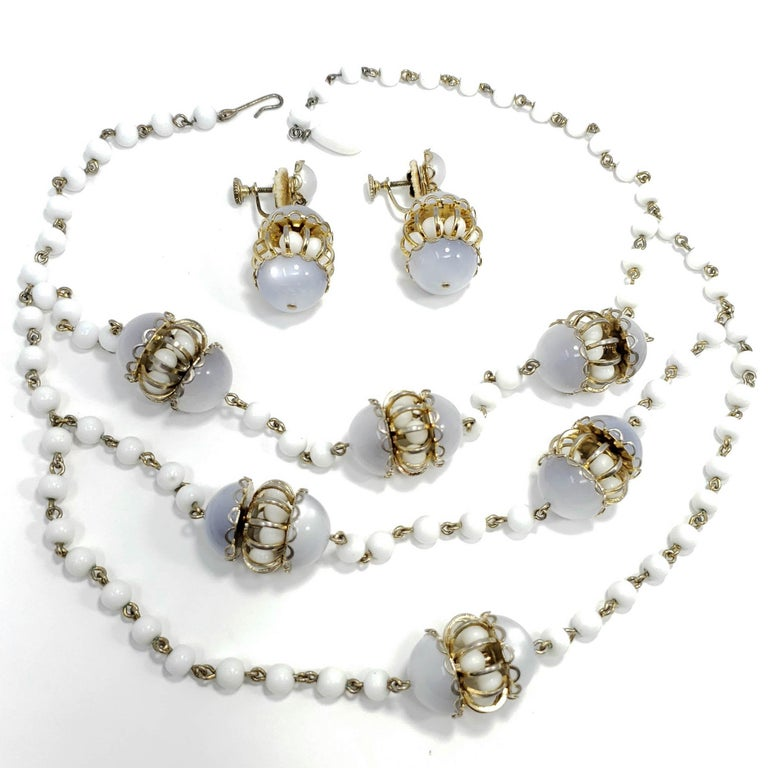 Matching moonglow lucite and milk glass bead multi-strand necklace and earring set. The necklace features decorative lucite and milk glass chamber charms set on a multi-strand milk glass bead necklace. Each earring features a matching charm, set on