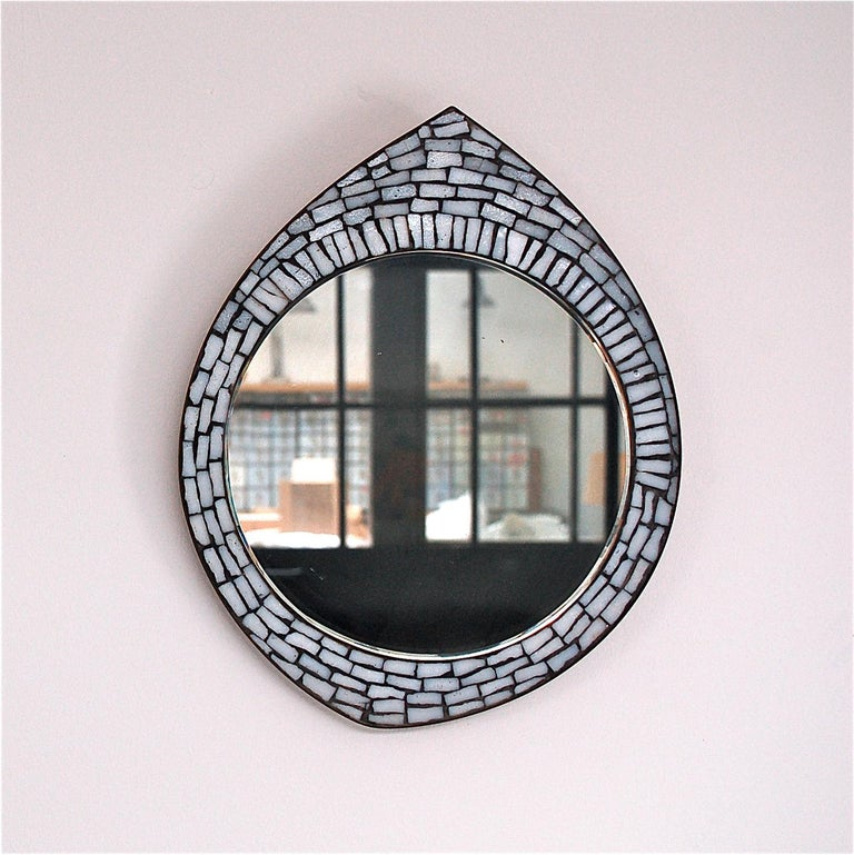 Midcentury white mosaic accent mirror in the style of Berthold Muller. The mirror has a shape that resembles a droplet, a tear drop. With the simple addition of an extra hook it can be hung horizontally to resemble an eye shape. Its dimensions are