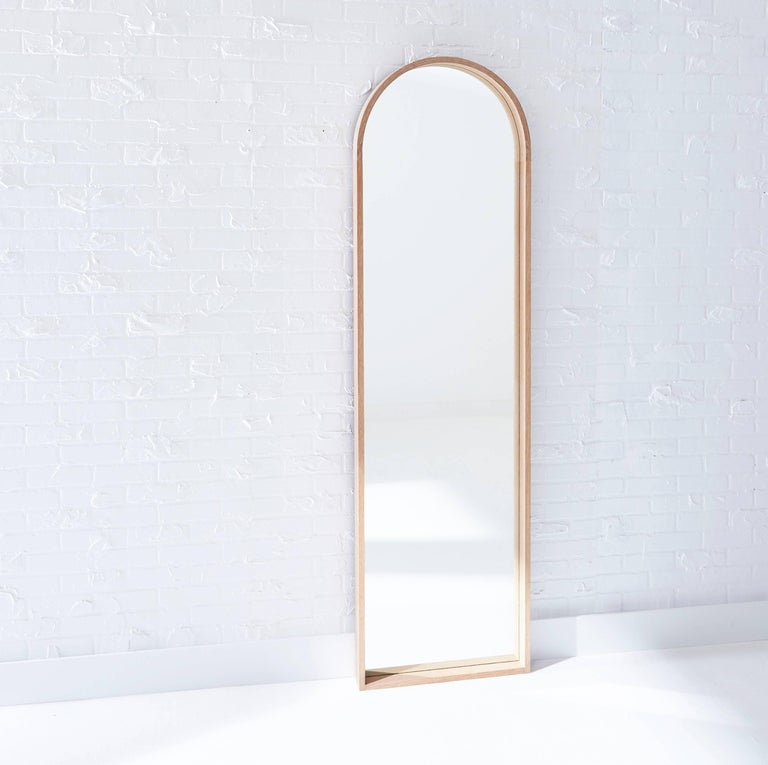 The contemporary Euclid mirror pays homage to the arched doorways that featured in Shaker architecture. The steam-bent arch is connected with brass pinned lap joints and the base of the frame features half-blind dovetails.The mirror floats off the