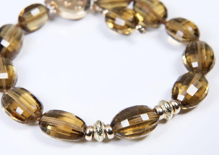 Faceted olives of golden quartz (6x14 mm) highlighted by 14kt yellow gold rondelles and the White Orchid Studio logo clasp, also in 14kt yellow gold.