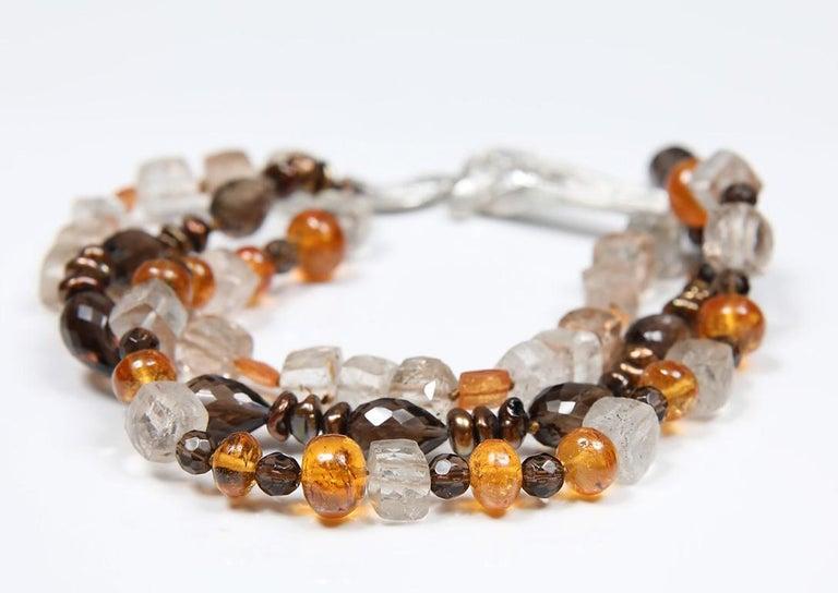 A three-strand bead bracelet of precious topaz enhanced with smoky quartz, mandarin garnet, and bronze Keshi pearls.  A silver, White Orchid Studio handcrafted vanilla bean clasp brings the bracelet together.