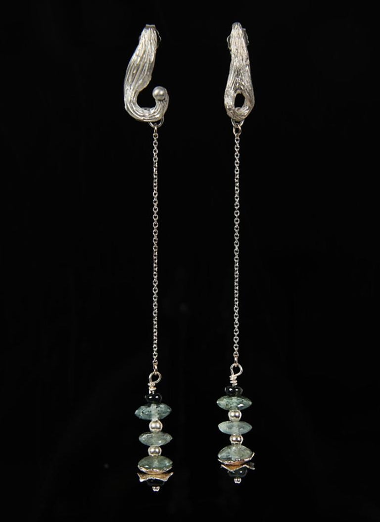 A stack of faceted moss aqua rondelles, blue-green sapphires, silver beads, and White Orchid Studio's hand-crafted silver spacers on a silver chain.  Silver White Orchid Studio's signature vanilla bean earrings encourage fun a swing as you move.