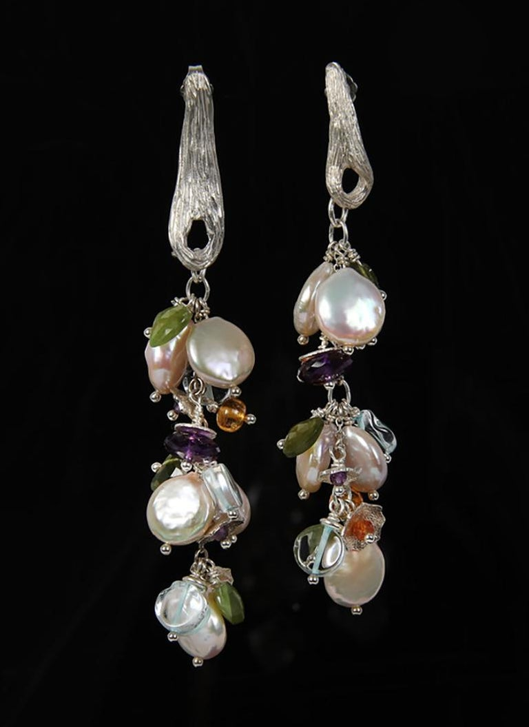 A dramatic cascade of pearls, aqua, mandarin garnet, idocrase, and amethyst swinging on different lengths of our White Orchid Studio's vanilla bean textured earrings in sterling.