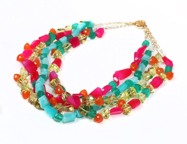 A four-strand riot of colors reminiscent of the color combinations made famous by Lilly Pulitzer. Carnelian, green and lemon quartz, amazonite, and neon pink chalcedony in a variety of shapes and sizes dance together on 14ky yellow gold chains,