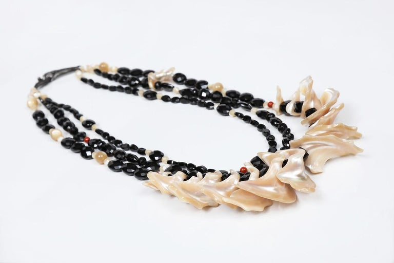 A dramatic three-strand bib of faceted black spinel and Mother of Pearl.  Look for unexpected shapes, configurations, along with pops of red jasper.  This necklace ends in White Orchid Studio's handcrafted, vanilla bean clasp in antiqued silver.