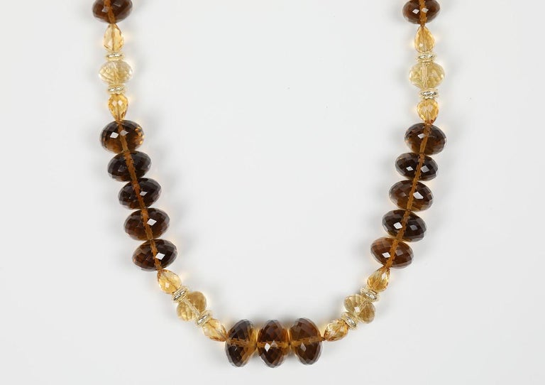 Lavish whiskey quartz (11 to 14mm) embraces three sizes and shapes of faceted citrine to create an opulent princess length necklace.  Complementary colors of the gems are warmed further by 14kt yellow gold spacers and finished by a White Orchid