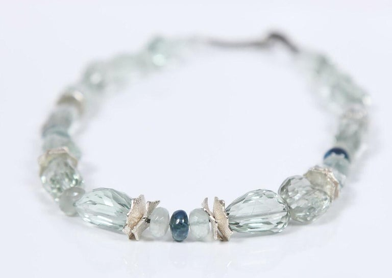 Icy, blue-green faceted prasiolite nuggets (21x19-10x15mm) reflect the beauty of blue-green kyanite (7mm) and Ceylon moonstone (7mm).  Pairings stand out thanks to White Orchid Studio's custom spacers in silver and our signature, handcrafted vanilla