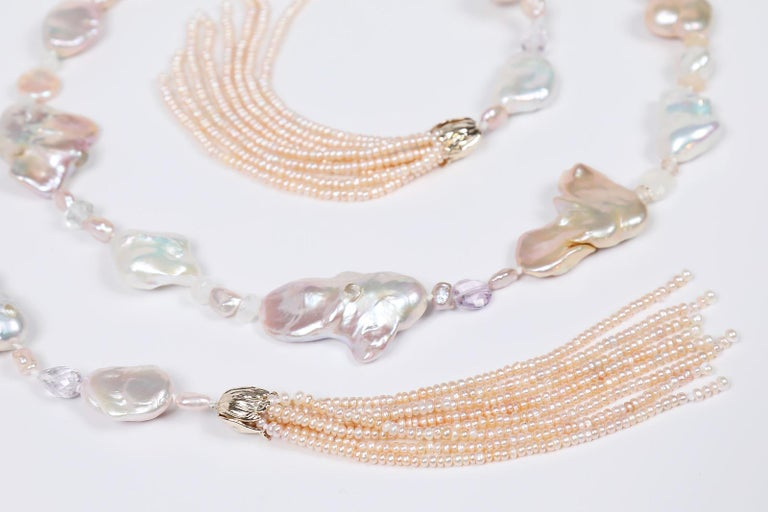 The iridescence of blush pink, freshwater Keshi pearls (15 to 26 mm) is accentuated by polished and faceted gems like lightly saturated amethyst, moonstone and Oregon sunstone.  Two handcrafted tassels of button pearls nestle under our 14kt yellow