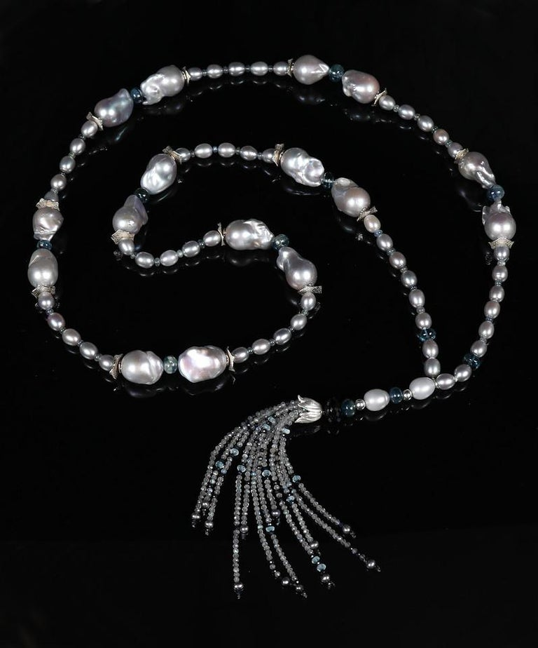 A sartoir of large (average size is 15 by 20mm), silver baroque freshwater pearls, silver rice pearls, polished kyanite rondelles and green-blue sapphires.  The baroque pearls are nestled between 2 sizes of our signature silver spacers.  The sartoir