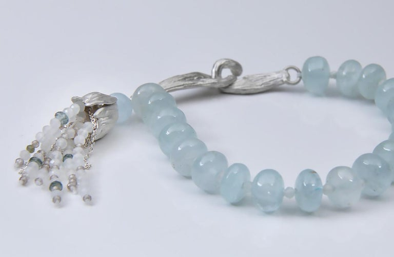 A soothing beaded bracelet of polished aqua and soft moonstone, adorned by a tassel of London blue topaz and two colors of moonstone, tucked under a silver White Orchid Studio, handcrafted bead cap.  The silver clasp is our handcrafted vanilla bean